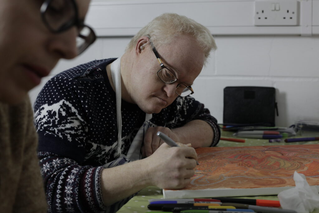 A white learning disabled man working on an artwork
