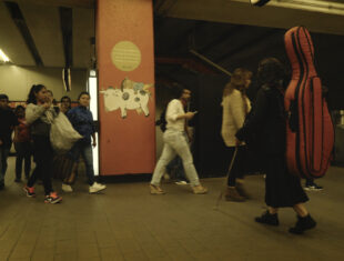 A color image of Maricarmen from the side inside a busy subway corridor, carrying a red cello case and a visually impaired stick.
