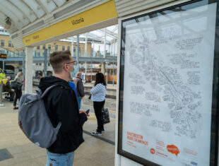 photo of a white man looking at a poster displayed on a metro platform