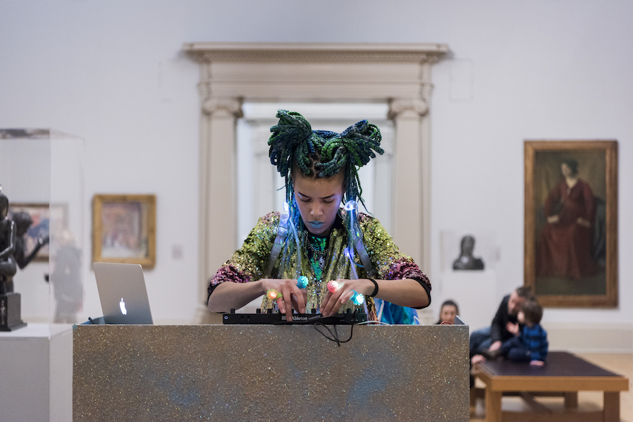 Photo of a woman artist of colour focusing on playing a digital instrument within a gallery setting