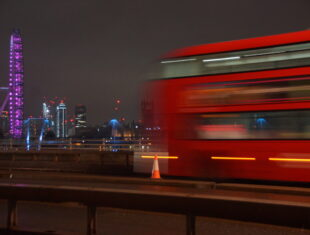 A blurred image of a red double decker bus crossing a bridge at night, the London Eye lit up with purple lights in the background.