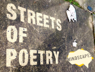 """A close up shot of a pavement. """"Streets of Poetry"""" has been stencilled onto the pavement."""