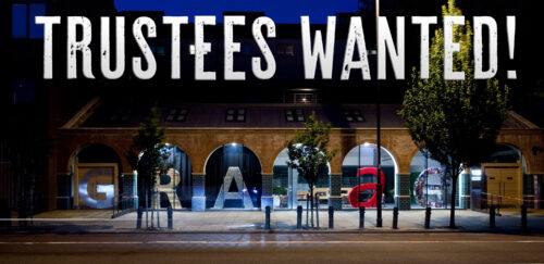 A photo showing the exterior of Graeae's Bradbury Studios at night. Giant coloured letters in arched windows spell out GRAEAE. Text overlaid at the top of the photo reads 'TRUSTEES WANTED'.