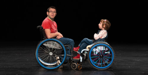 A man in a red t-shirt on the left and a child in a white floral top and denim dungarees on the right sit facing each other in blue wheeled wheelchairs.