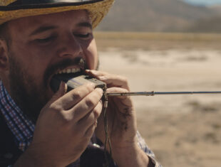 A close up color image of El Niño de Elche biting a dusty and sandy old radio by holding it up with both hands. He is wearing a straw hat, a blue and red checked shirt and a balck vest. In the background a sunny desert landscape out of focus