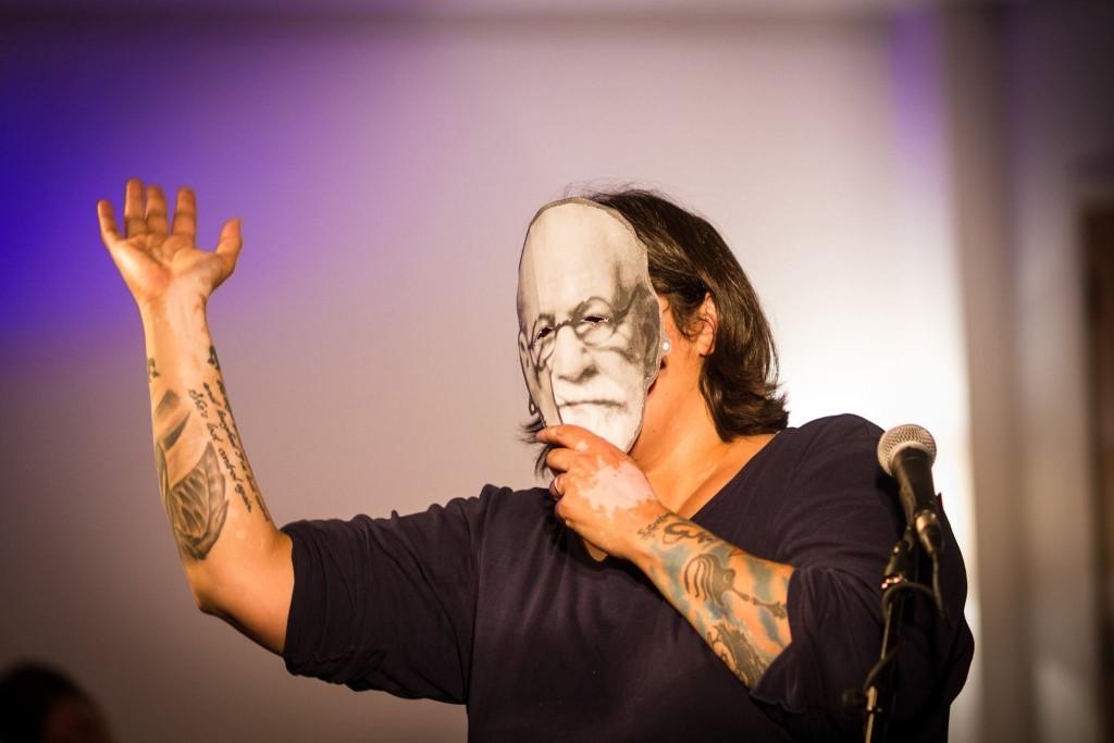 Dolly Sen holding a mask of Sigmund Freud over her face