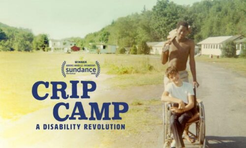 Film poster for Crip Camp shows a black young man with a guitar pushing a white boy in a wheelchair