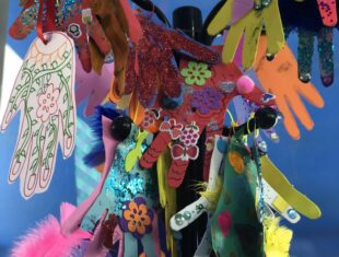 Multi coloured paper hands and hung from a mobile on a blue ceiling