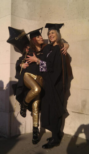 Two white woman smiling and embracing at a masters degree ceremony
