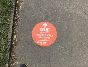 photo looking down on an orange sticker on the pavement, next to a pair of shoes