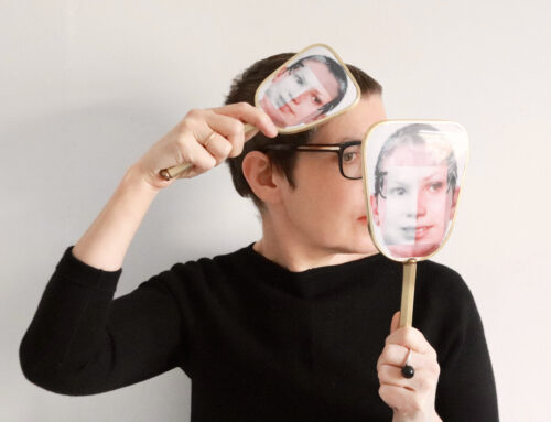 A white woman holds two vanity mirrors which have photographs on them up in the air, obscuring her face