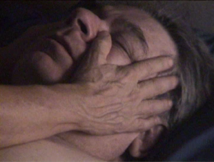 The face of a white, middle-aged man with short grey hair (Stephen Dwoskin), with his eyes closed. His left cheek is being caressed by the right hand of an older white woman.