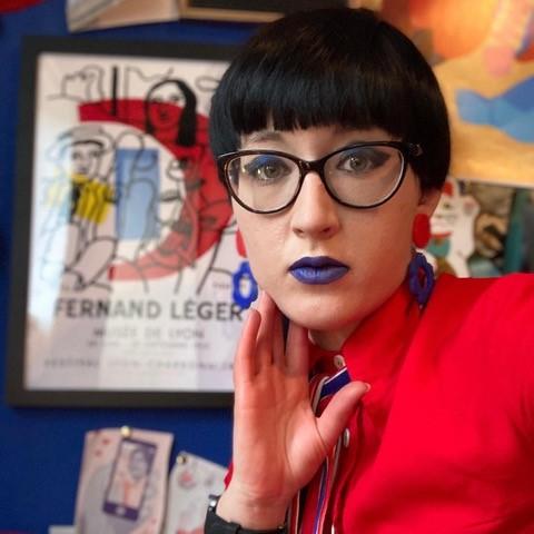 White non-binary person with black hair, glasses and blue lipstick
