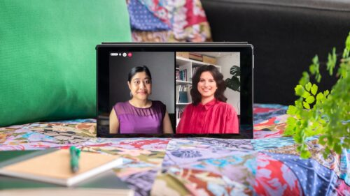 """Photograph of a laptop sitting on a sofa next to a notepad and pen. The sofa has a multicoloured patchwork quilt with a green cushion. On the laptop screen is a live event showing Khairani Barokka who has dark hair tied back and is wearing a purple top. On the right is Bárbara Rodríguez Muñoz who has shoulder-length brown hair and is wearing a red shirt. In the top left-hand corner of the screen is a red telephone icon with other video call icons """"People"""" and """"chat""""."""