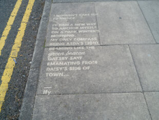 Photograph of white text printed on grey pavement slabs, double yellow lines to the left.