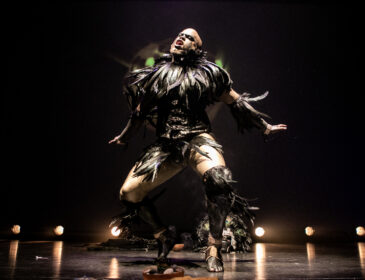 Black performer Lasana Shabazz in the middle of a bare stage with some bright lights is engaged in an intense dance, wearing costume adorned with black leather and large black feathers