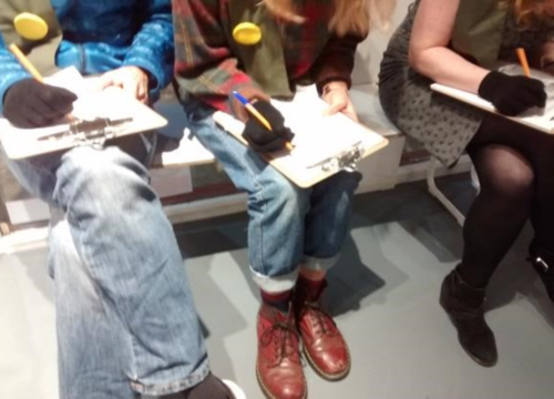 Photograph of three seated players trying to fill in questionnaires on clipboards on the laps,whilst wearing black woolly gloves on their writing hand.