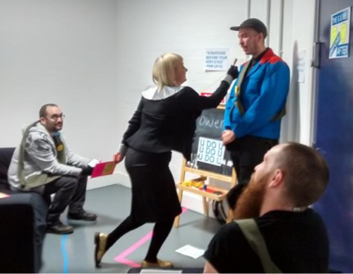 An action photo of a blonde woman pointing towards the face of the official looking man she is approaching