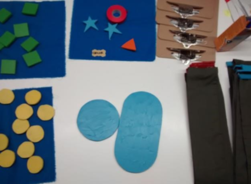 Photo of a white table top with coloured felt badges of different shapes laid out on blue paper