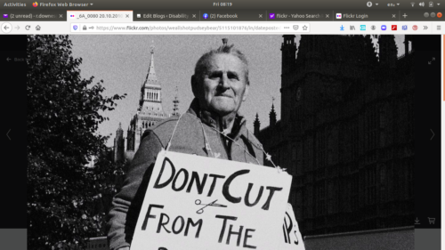An old man standing in front of the houses of parliamnet with a protest sign around his neck