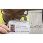A man wearing a yellow builders helmet holds a name badge to the camera. On it is written; Aaron Williamson, Strategic Quotas Consultant, Lofty Management