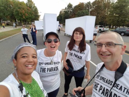 Four people are looking directly at the camera and smiling. They are on the streets of Philadelphia in broad daylight. Behind them, volunteers are wheeling lightboxes as part of Spit Spreads Death: The Parade, a 2019 work by Blast Theory. In the foreground are Matt Adams and Ju Row Farr of Blast Theory with two Philadelphia residents, all wearing white t-shirts reading Spit Spread Death: The Parade