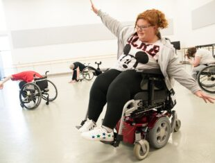 A wheelchair user is dancing in a dance studio with her arms outstretched