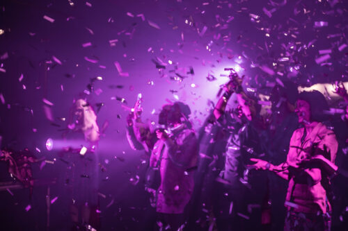 Three people are bathed in purple light. They are smiling, clapping and cheering. The air is filled with confetti.