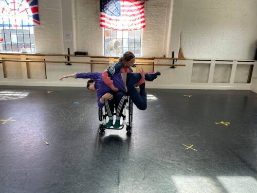 Two dancers in a dance studio. One is a wheelchair user. She is holding another dancer in a lift so her whole body is off the ground and horizontal. One arm is out stretch the other bent. One leg extended and the other bent. Both are female dancers in the 20's, both with brown hair (one short and one long). The photo is taken in a rehearsal. Both dancers are skilled professional dancers who both identify as disabled. The lift requires great skill.