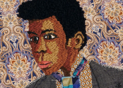 A textile work of a person wearing a grey suit and multicoloured tie.