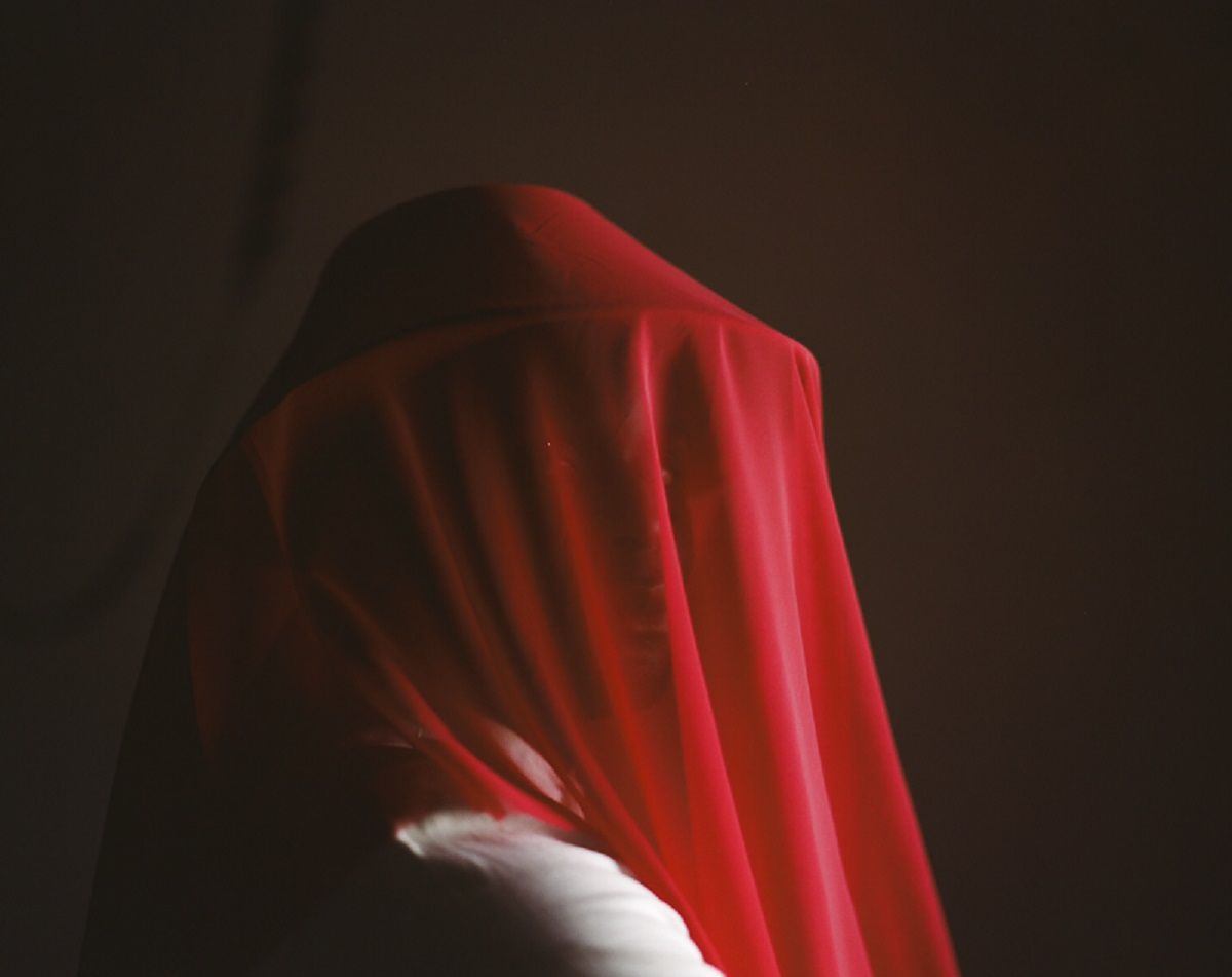A black man wearing a red hat with a red veil which covers his face