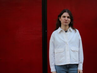 A white woman wearing a white shirt and blue jeans with shoulder length brown hair stands in front of a red wall.