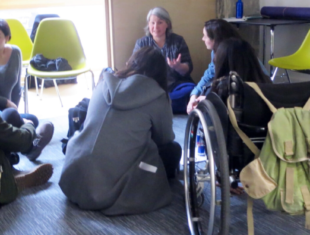 A group of women sit on the floor talking. There is a wheelchair in the foreground and yellow chairs around the room.