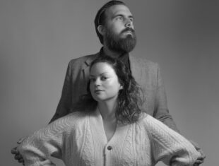 Black and white portrait of a white woman wearing a chunky cardigan with her hands on her hips. She has shoulder length wavy hair. Behind her stands a man in a suit. He has short hair and a beard.