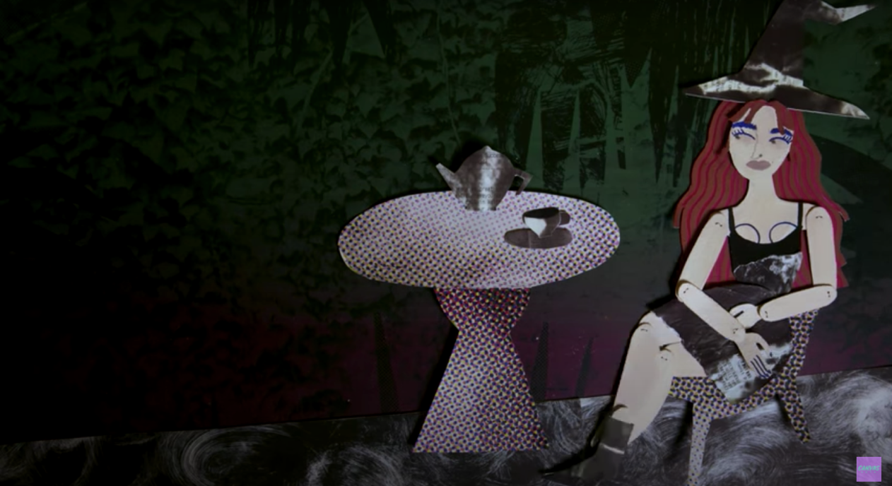 Still from an animated film showing a witch sitting at a table