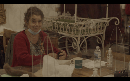 Still from the film Sounds at the Edges, featuring a woman and some art materials