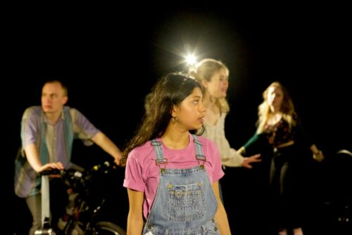 Four young people onstage, the foremost of which has long brown hair, wears denim dungarees with a pink tshirt and is looking offstage to her left. The others are out of focus in the background.