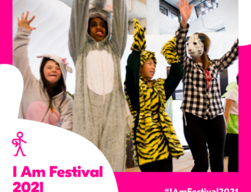 Four young people taking part in a workshop at I Am Festival 2018. Three are wearing onesies and one is wearing a white mask.