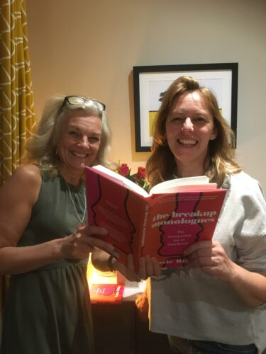 Two white women read from a book whilst smiling