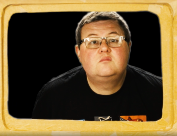 A white man with short brown hair wearing glasses and a black Tshirt looking out of a TV