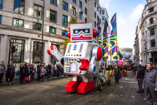 A photo of a large robot at a street parade.