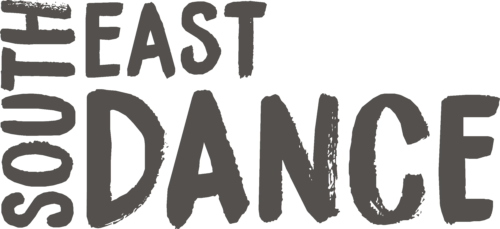 'South East Dance' written in charcoal, bold font with a white back ground. 'South' is written vertically on the left side, with 'East' written to the right and 'Dance' underneath.