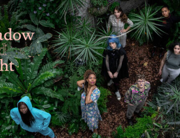 Seven Guildhall School PACE artists, standing spaced out and looking up at the camera, surrounded by Green foliage. The words 'of shadow and light' appear in orange in the top left hand corner of the image
