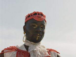 A black man wearing traditional African dress with a red beaded hat. he also has gold make up on his face