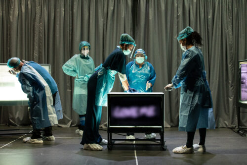 Nurses and doctors in scrubs and masks on a stage