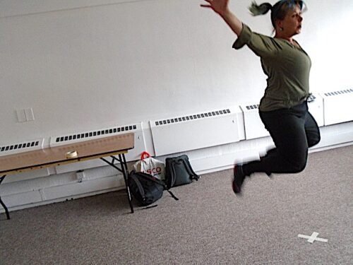 photo of a white woman mid-jump in an empty room