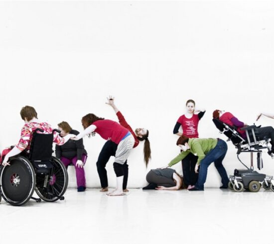 there is a group of people at a white wall in a line. Some are sitting in wheelchairs, some are sitting in chairs and some are standing