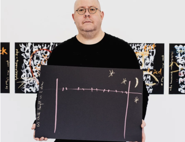 white male artist stands in front of a seris of paintings