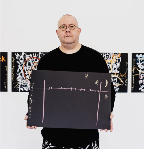 white male artist stands in front of a series of abstract paintings