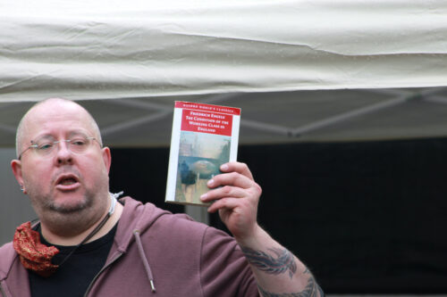 white male stands holding a book in their right hand